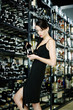 Woman choosing wine in a wine cellar