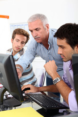 College lecturer showing students something on the computer