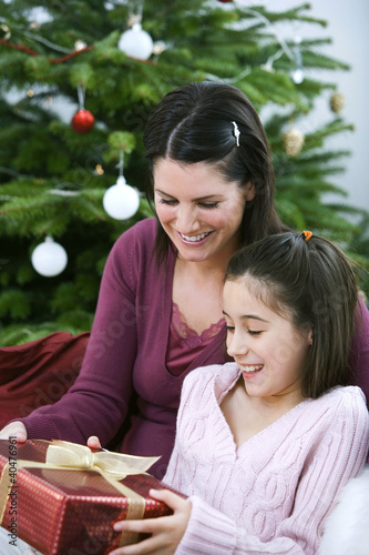 Little girl receiving a Christmas present from her mother