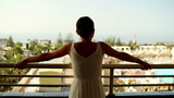 Woman walking out on hotel balcony and looking around