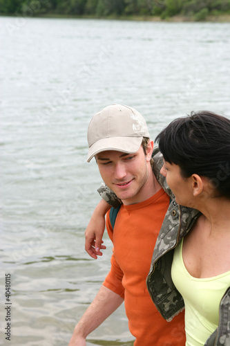 Young couple walking by a river