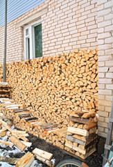 firewood near wall of the rural building