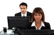 Two office workers sat at their desks