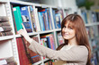 young adult student selecting book in library