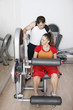 Woman exercising on gym equipment, personal trainer assisting her
