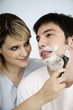 Woman shaving man's face