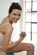 Woman sitting on fitness ball, lifting dumbbell