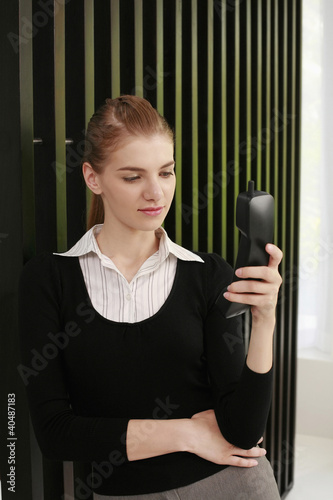Woman in formal wear using cordless phone
