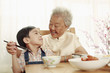 Senior woman helping boy to eat using with chopsticks