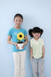 Girl holding sunflower plant with another girl beside her