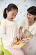 Woman showing girl alphabet puzzle