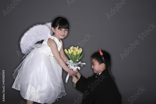 Boy with tuxedo and devil horns giving flowers to girl wearing white dress and angel wings