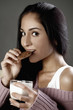 Woman biting on a cookie and holding a glass of milk