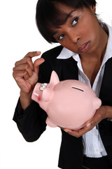 A businesswoman holding a piggy bank.