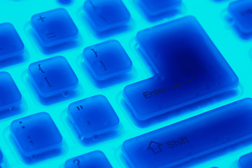 Fragment of  blue backlit flexible keyboard with enter and shift