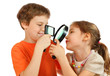 Brother and sister looking at each other through loupe