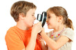 Brother and sister look at each other through magnifying glasses