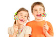 Happy brother and sister hold colorful lollipops isolated
