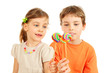 Happy brother and sister hold colorful lollipops