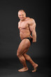 Undressed smiling bodybuilder demonstrates arms and legs muscles