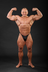 Undressed tanned smiling bodybuilder demonstrates his arm muscle