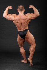 Undressed bronzed bodybuilder shows the muscles of hands