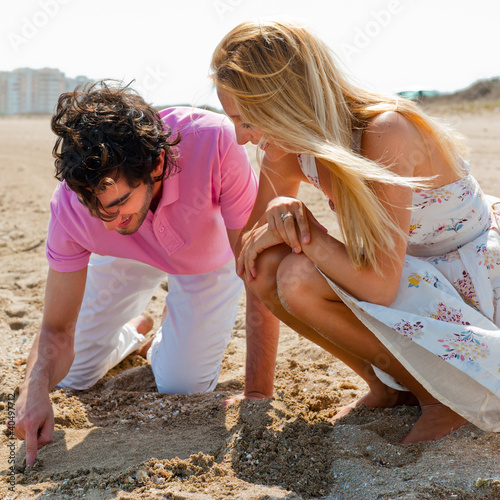 Couple in love drawing a heart in the sand at beach