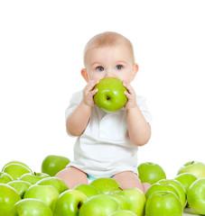 Adorable baby sitting among fresh fruits and eating green apple.