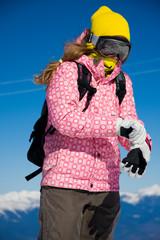 Snowboarder girl dressing gloves