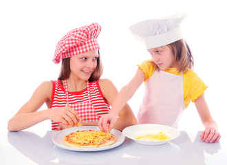 Two kids dressed as chefs preparing a pizza - isolated