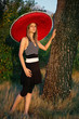 Young girl with a sombrero leaning on a tree