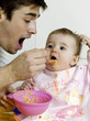 Father feeding baby girl