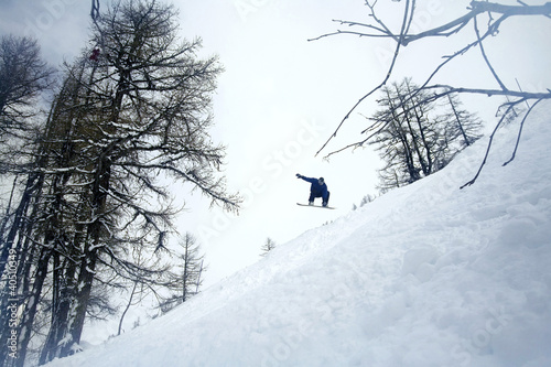 Man jumping in mid air on snowboard