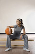 Woman sitting on bench with a basketball