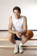 Man sitting on bench, basketball beside him