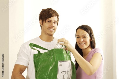 Man and woman with glass and plastic bag for recycling