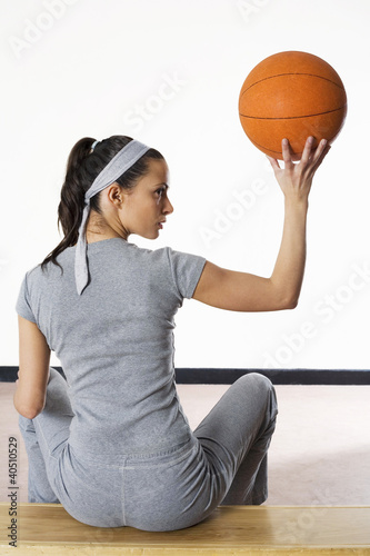 Woman sitting on bench holding up basketball