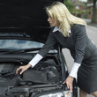 Businesswoman looking under car hood