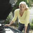 Woman with lug wrench looking under car hood