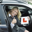 Businesswoman showing thumbs up while holding L plate