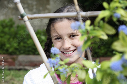 Girl looking through wooden post with flowers