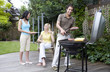 Man and women having barbeque in the garden