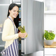 Woman taking out asparagus from the refrigerator