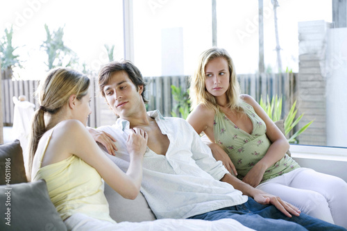 Фото: Man and two women relaxing on the sofa