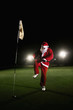 Man in santa suit trying to break a golf club