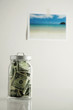 Bank notes in a transparent jar, picture of a beach hanging on the wall in the background