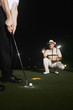 Two men playing golf at night