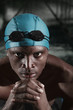 Man with swimming cap and goggles staring at the camera