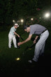 Two men searching for golf ball at night