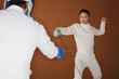 Woman with fencing foil dodging her opponent's attack